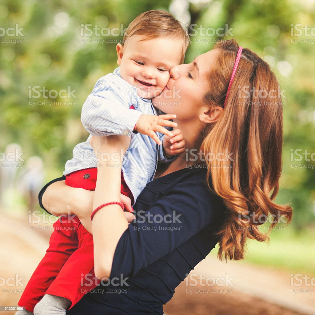 Mother kissing her baby boy stock photo