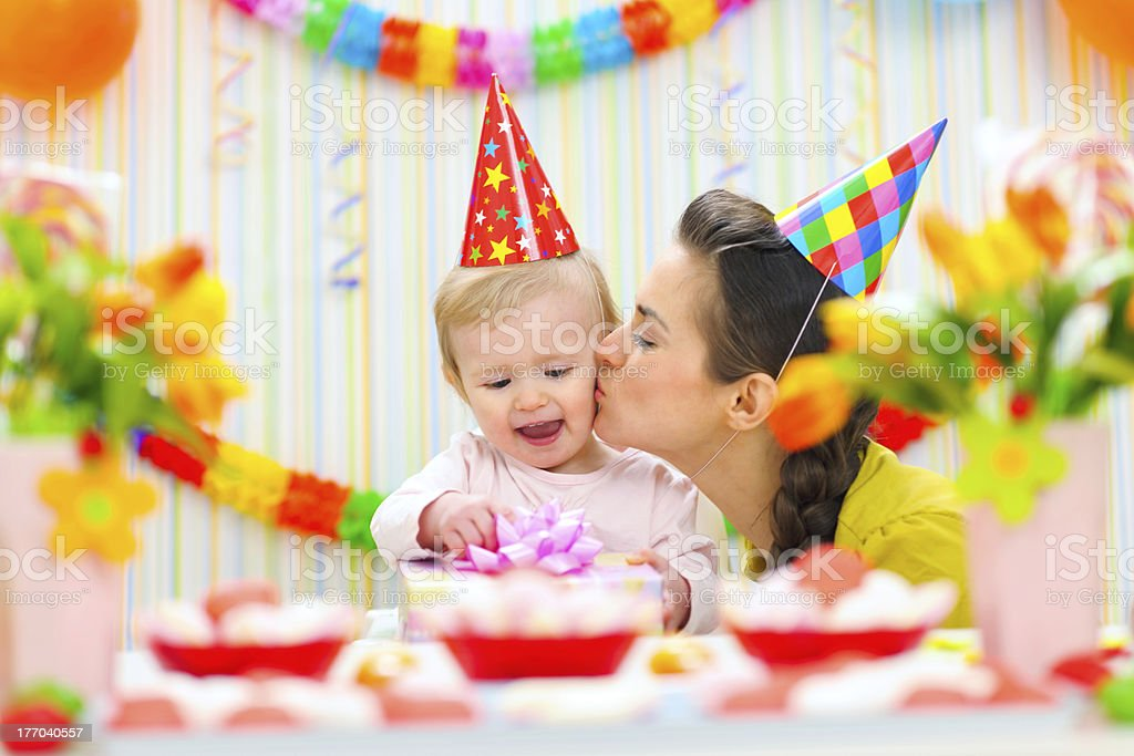 Mother kissing her happy while baby checking present stock photo