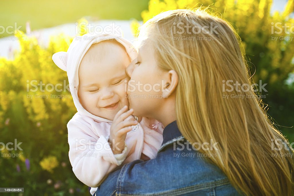 mother kissing her little daughter royalty-free stock photo