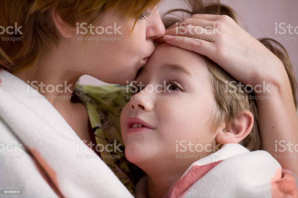 Mother kissing her son on the forehead stock photo