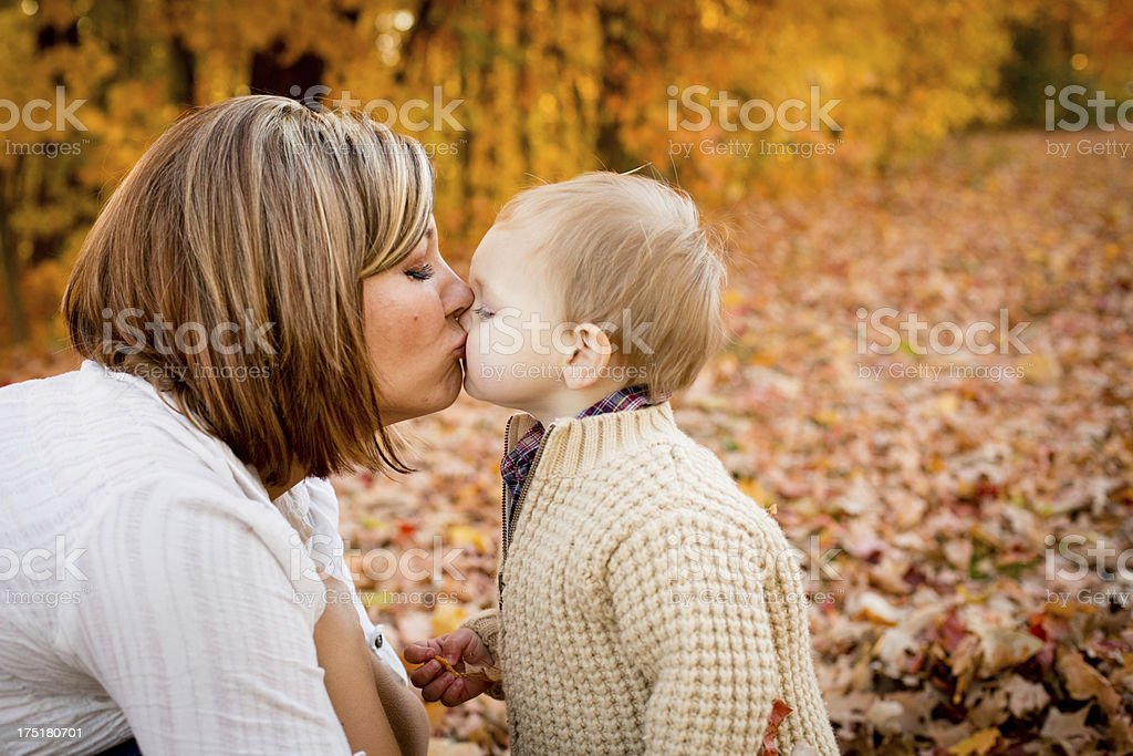Mother Kissing Little Son While Outside on Fall Day royalty-free stock photo