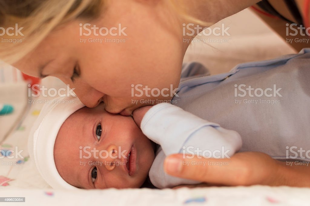 Mother kissing newborn baby boy stock photo