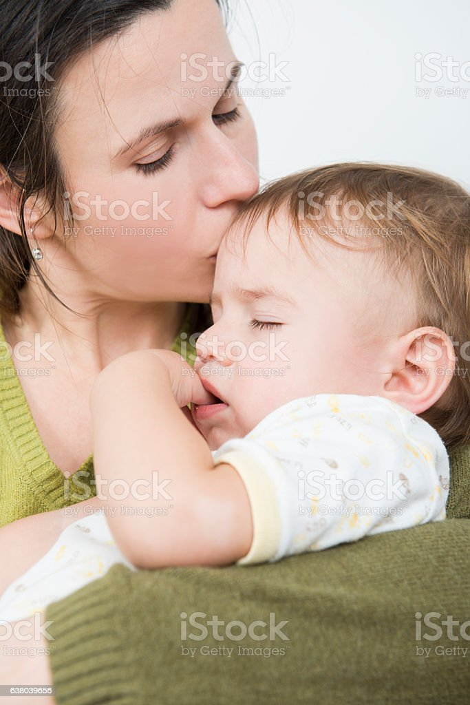 Mother kissing sick baby stock photo