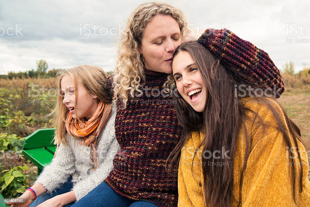 Mother kissing teenage daughter strolling in trailer in field. stock photo