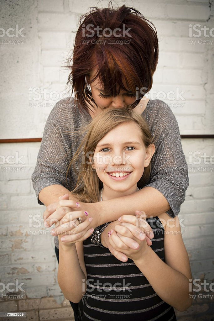 Mother Kissing Top of Daughter's Head, in Outdoor Setting stock photo