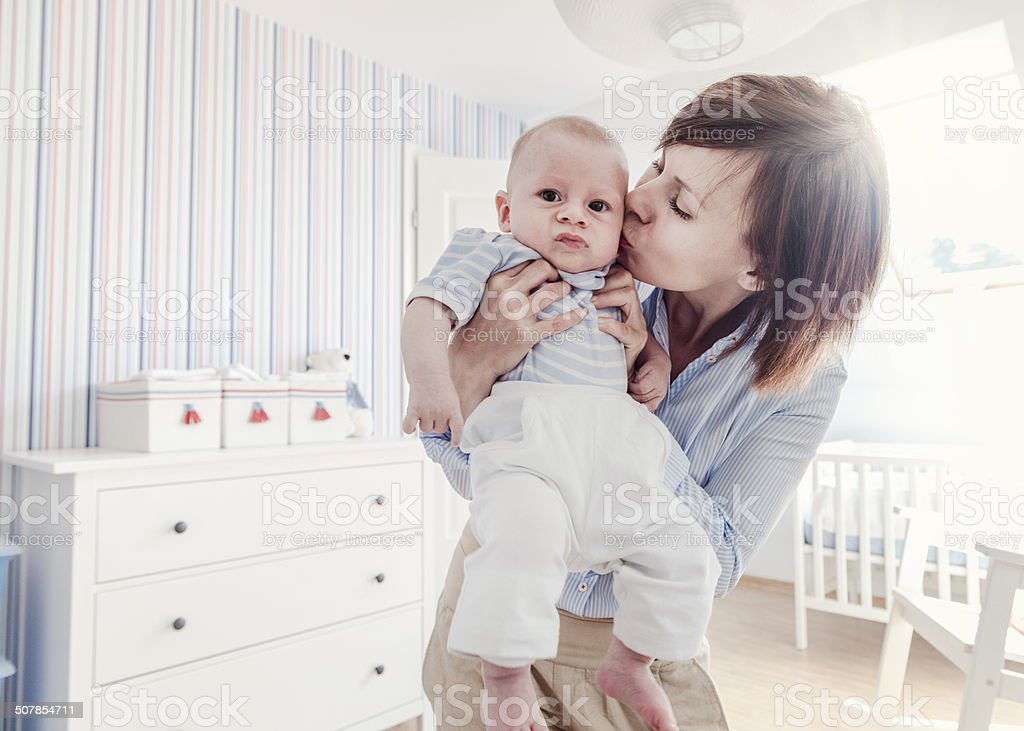 Mother kissing unhappy little baby boy, home interior, retro look stock photo