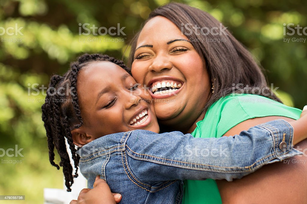 Mother laughing and hugging her daughter stock photo