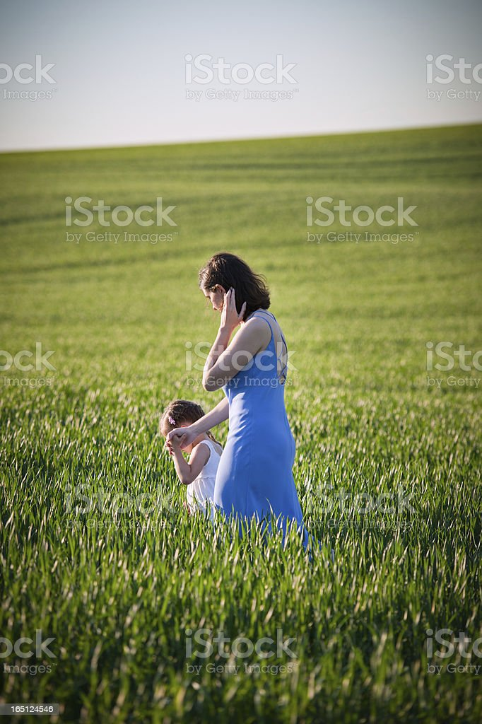 Mother Leading Daughter Through Fresh Spring Field stock photo