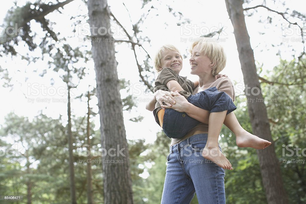 Mother lifting son in woods royalty-free stock photo