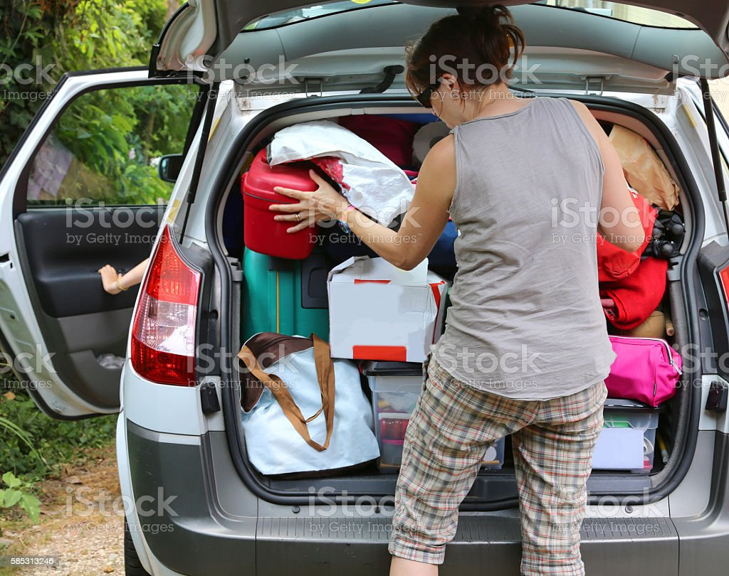 mother loads the luggage in the trunk of the car stock photo