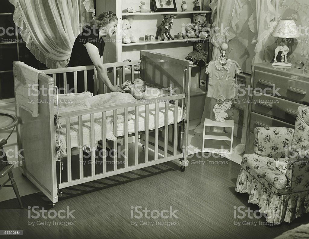 Mother looking at baby (3-6 months) lying in crib, (B&W) royalty-free stock photo