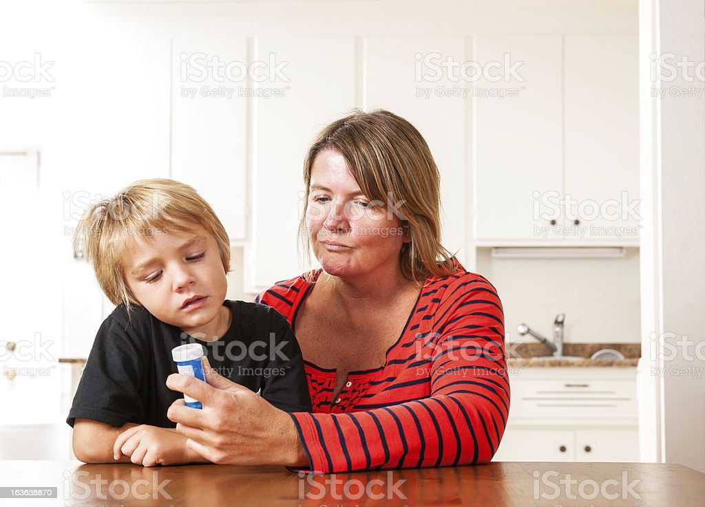 Mother looking at prescription medication with her son royalty-free stock photo