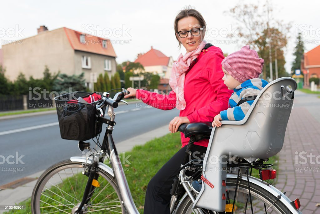 Mother looks at her son in bicycle seat stock photo