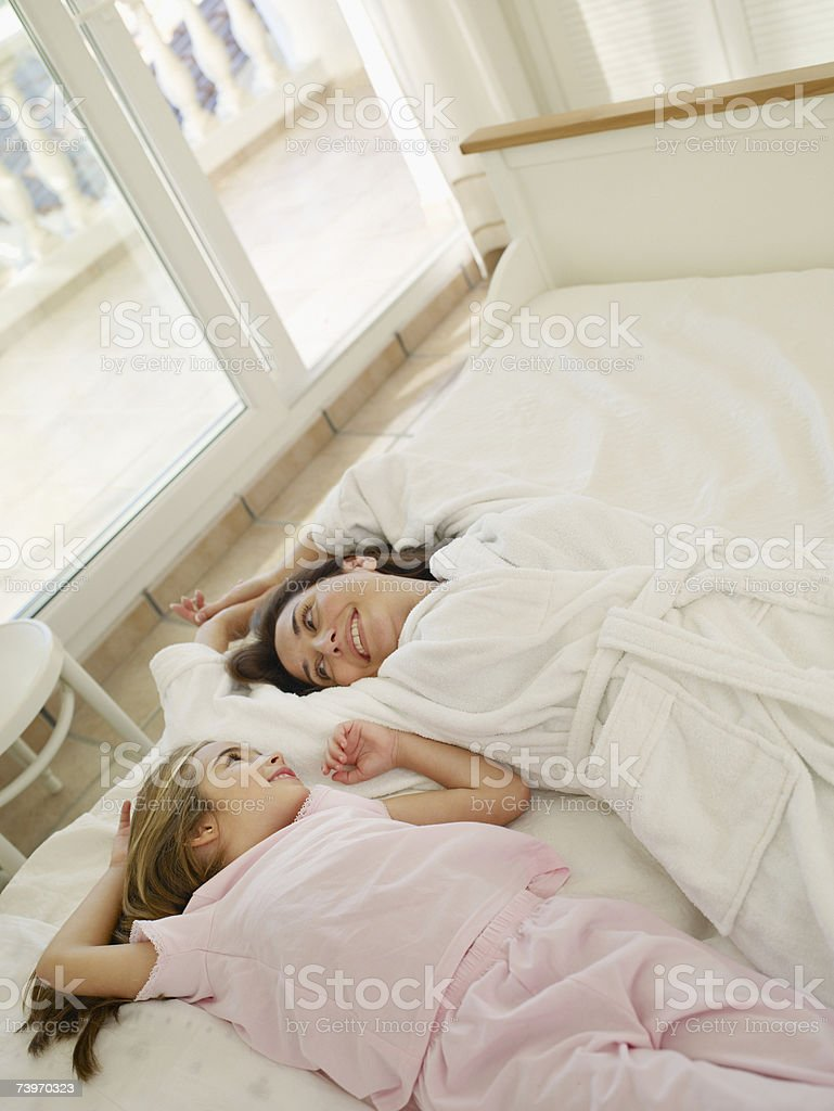 Mother lying on bed with young daughter royalty-free stock photo