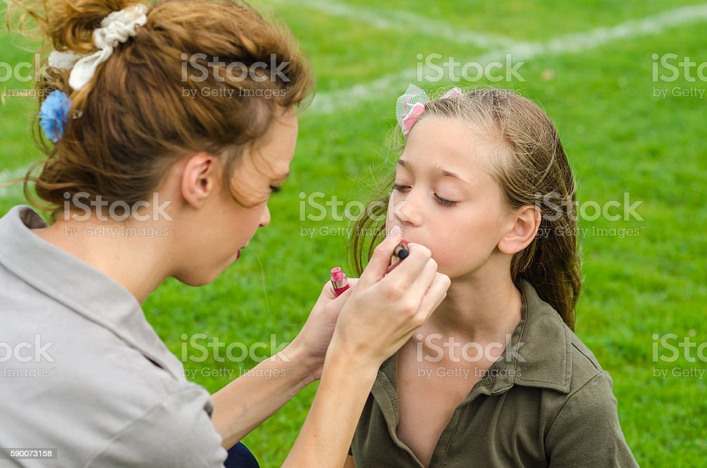 mother makeup her daughter in nature stock photo