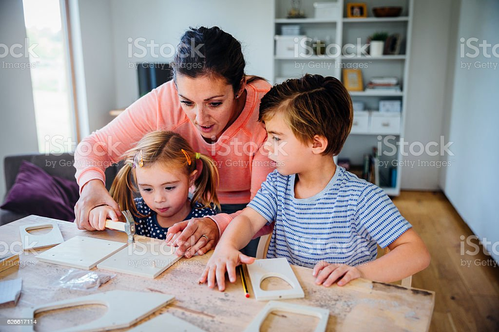 Mother Making a Bird Box with her Children stock photo