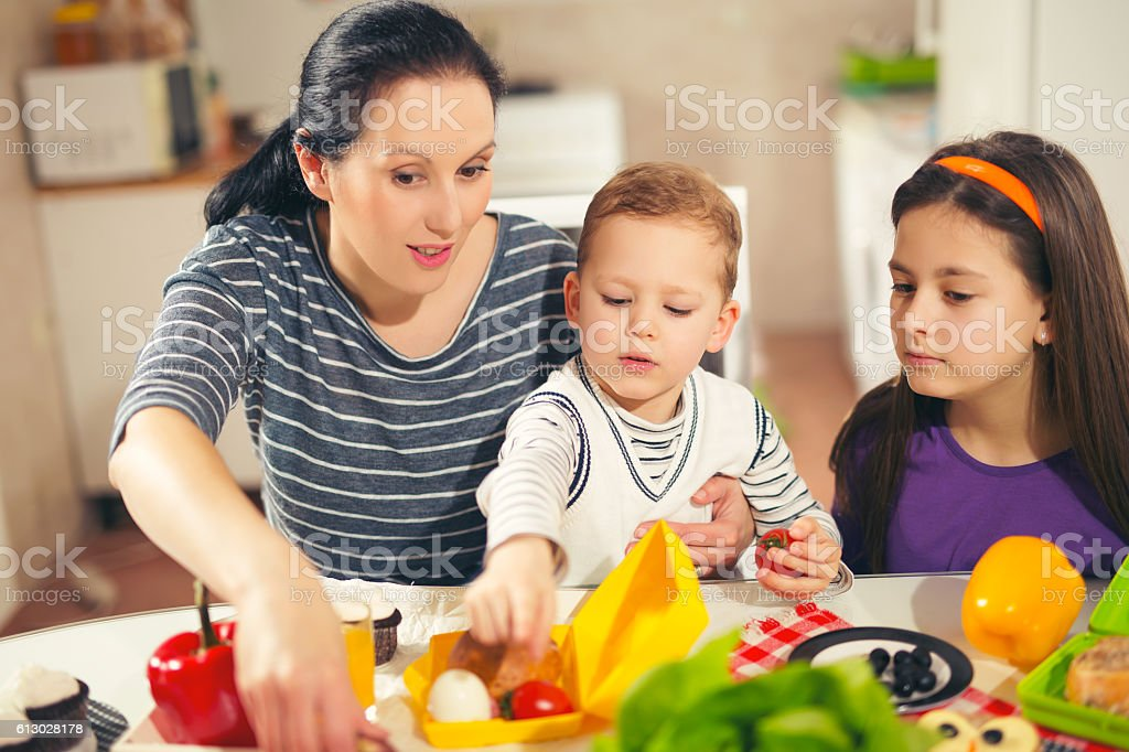 Mother making breakfast for her children in the morning stock photo