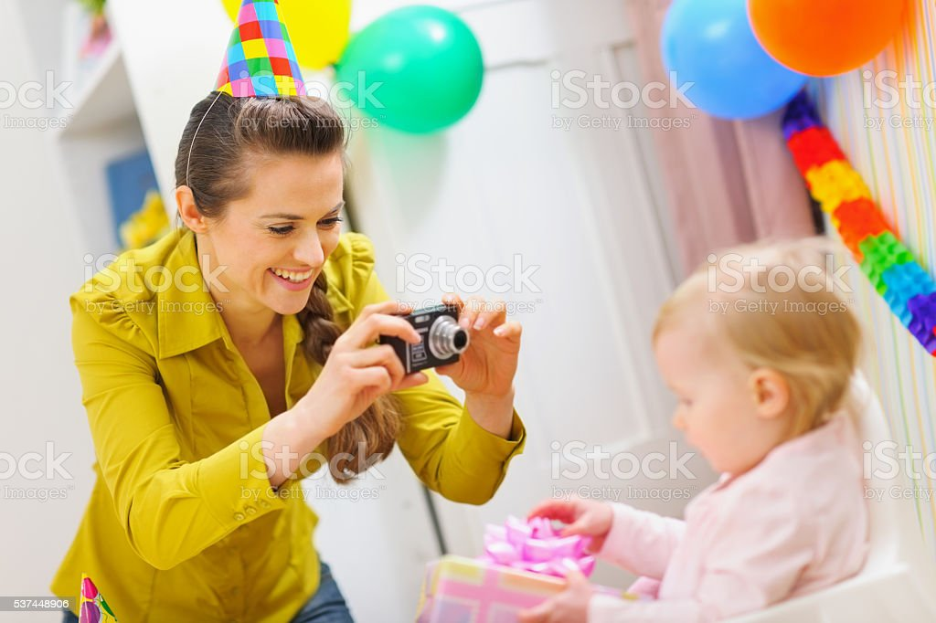 mother making photos at babies birthday party stock photo
