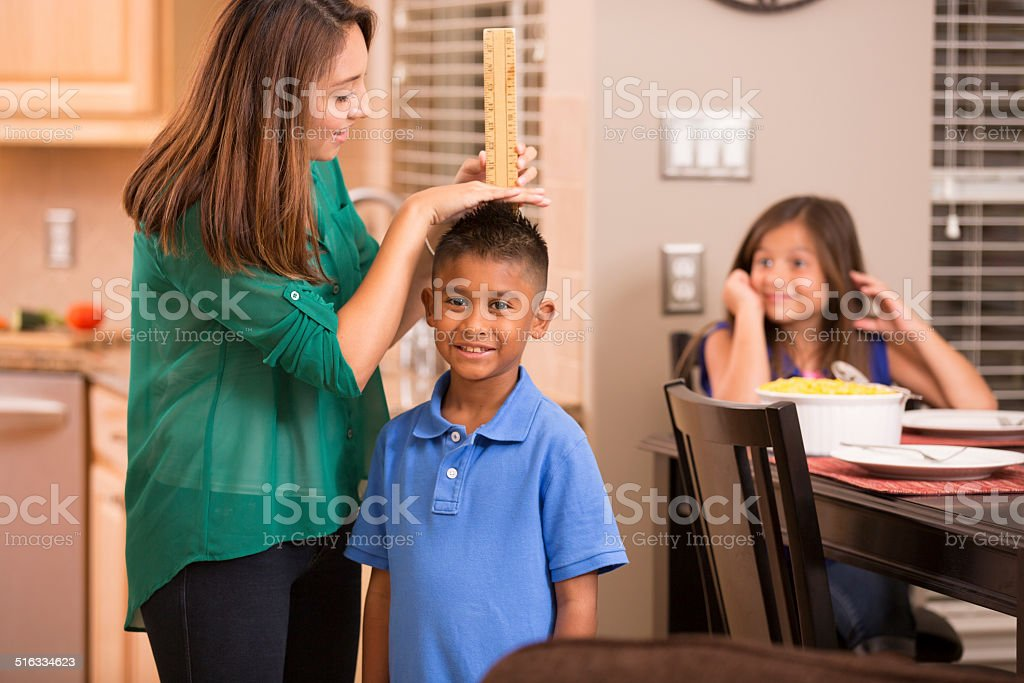 Mother measures growing son's height with yard stick. Home. stock photo