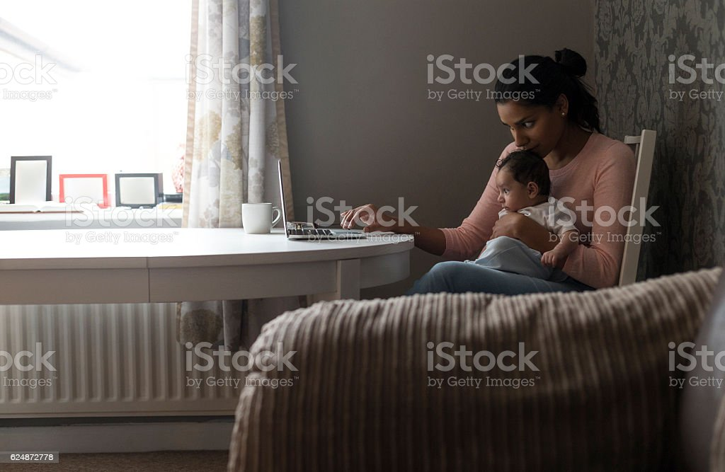 Mother multi-tasking work and baby stock photo