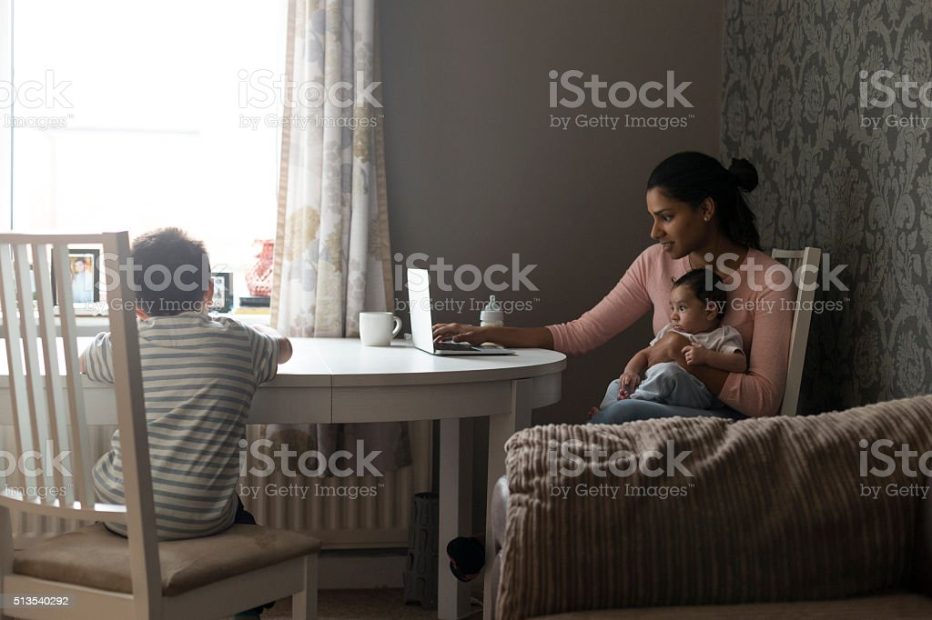 Mother multi-tasking work and children stock photo