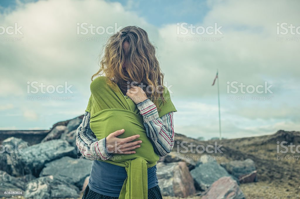 Mother on rocks with baby in wrap stock photo