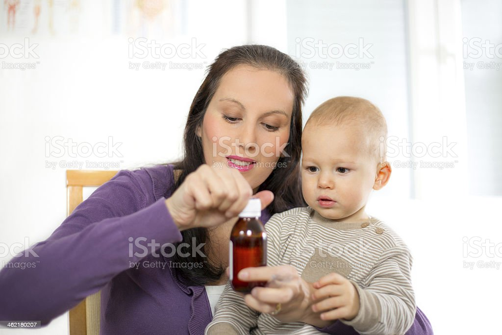 Mother opening a bottle of medicine for her child stock photo