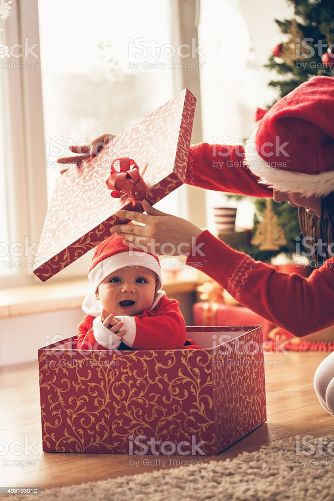 Mother opening Christmas present with baby stock photo