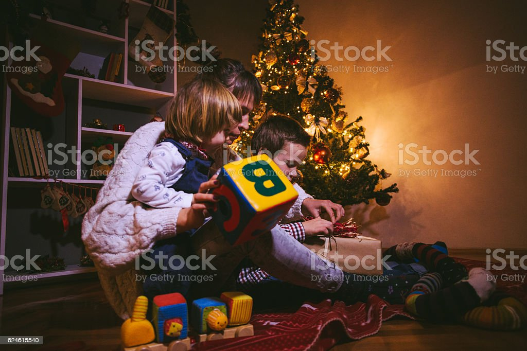 Mother Opening Christmas Presents With Two Children stock photo