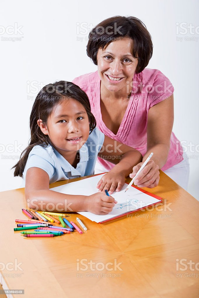 Mother or teacher helping little girl with school work royalty-free stock photo