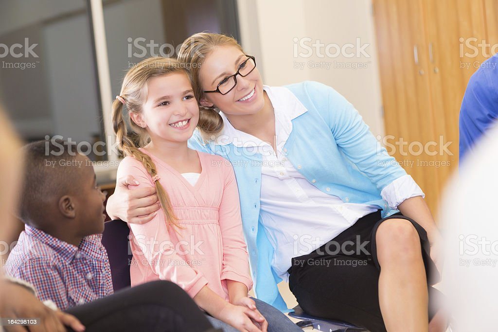 Mother or teacher hugging young girl in group meeting royalty-free stock photo