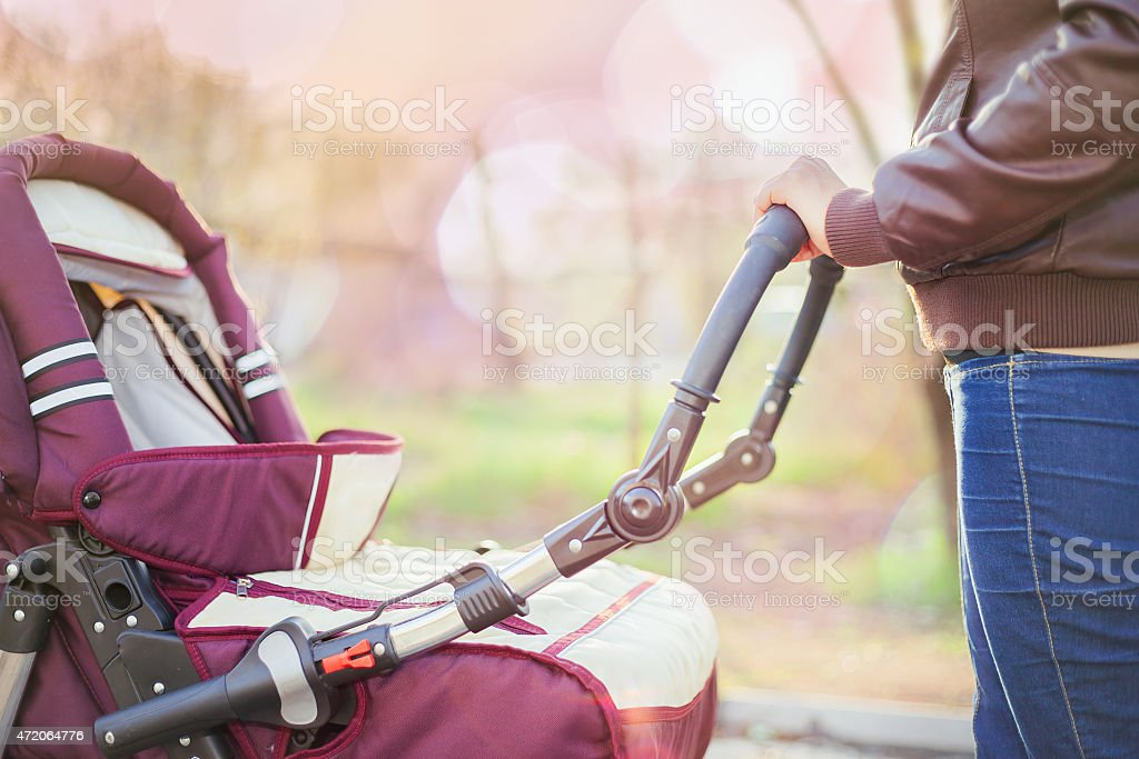 Mother outdoors holding a baby carriage stock photo