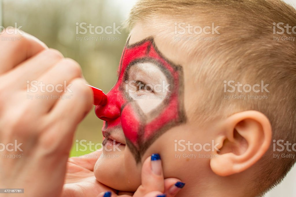 Mother painting her son's face for Carnival stock photo