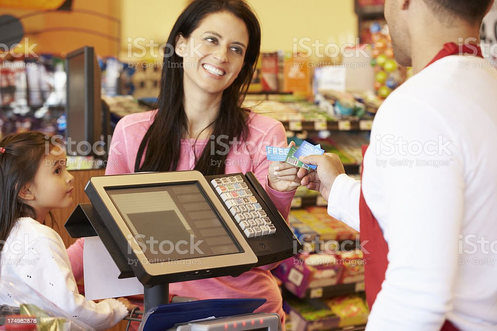 Mother Paying For Family Shopping At Checkout With Card royalty-free stock photo