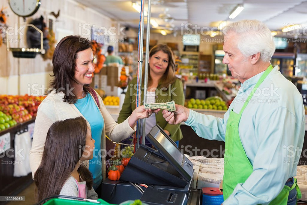 Mother paying for groceries in local market stock photo