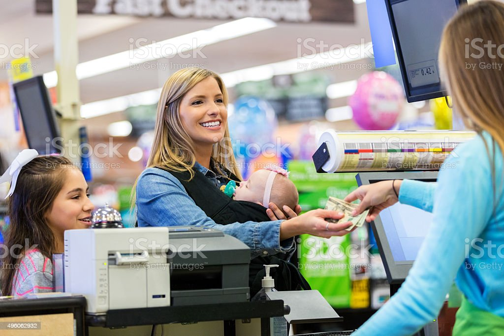 Mother paying for groceries while shopping with daughter and baby stock photo