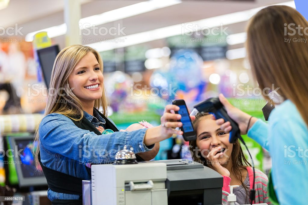 Mother paying for groceries with smart phone app in store stock photo