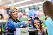 Mother paying for groceries with smart phone app in store