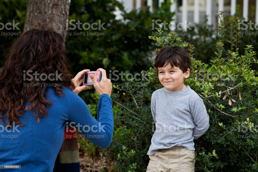 Mother photographing little boy stock photo