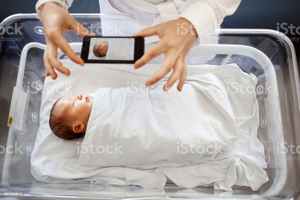 Mother photographing newborn son stock photo