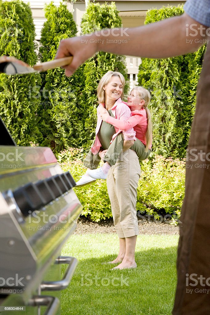 Mother piggyback with daughter at home during backyard cookout stock photo