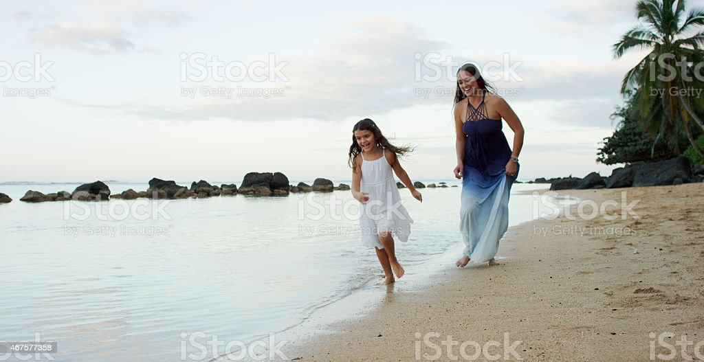 Mother Playfully Chasing Daughter stock photo