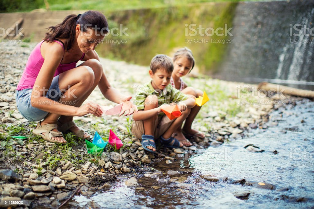 Mother playing paper boats with her childs stock photo
