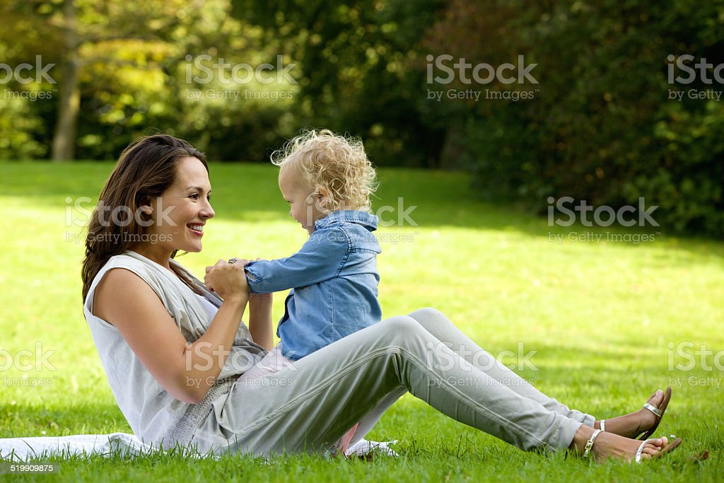 Mother playing with cute baby outdoors stock photo