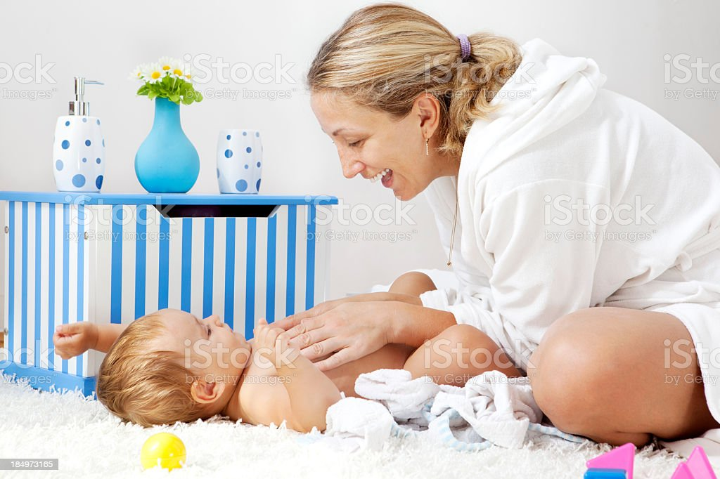Mother playing with her baby girl daughter after bath stock photo
