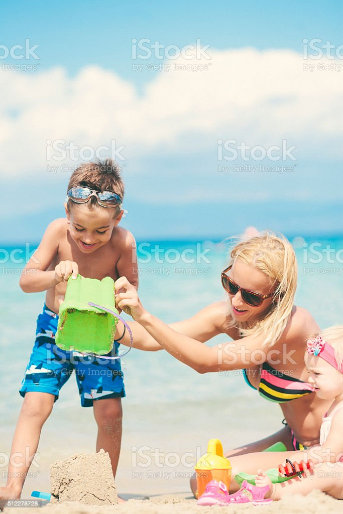 Mother playing with her children with sand at the beach stock photo