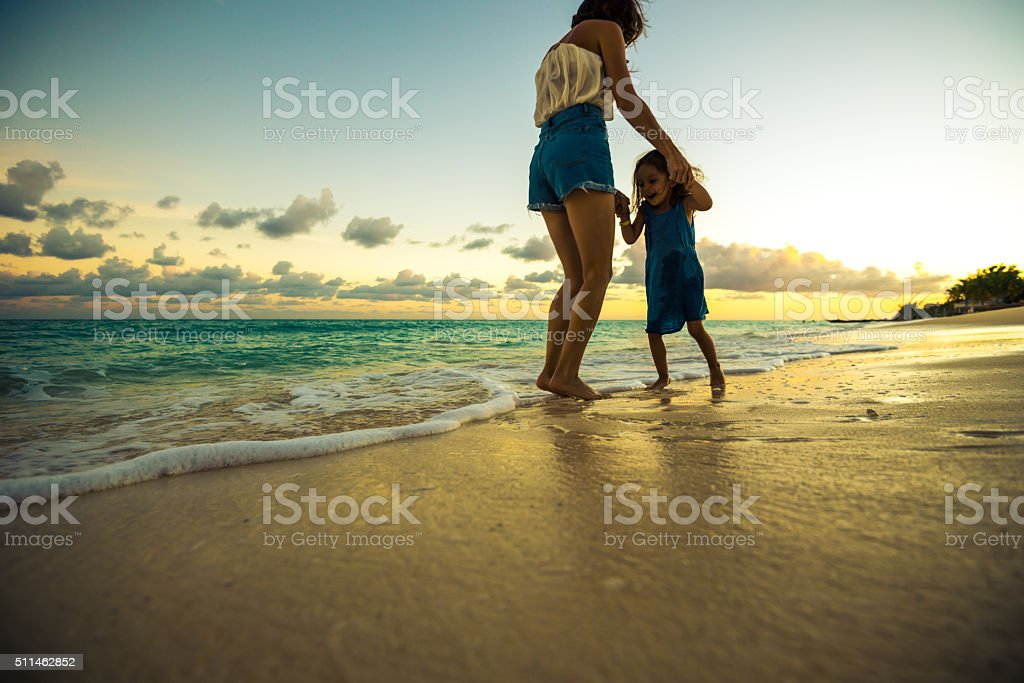 Mother playing with her daughter on the beach at sunset stock photo