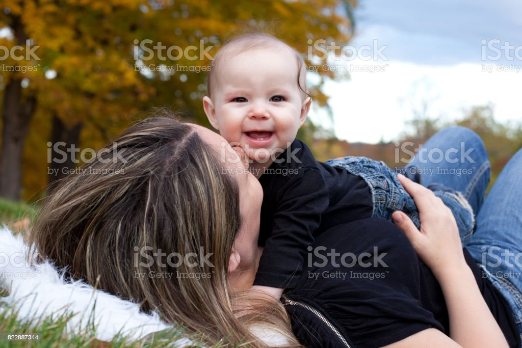 mother playing with laughing baby stock photo