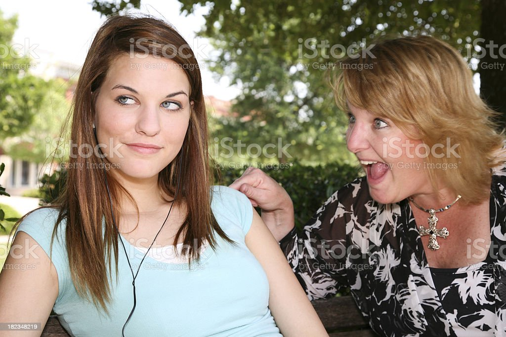 Mother pointing and yelling at daughter who is turning away royalty-free stock photo