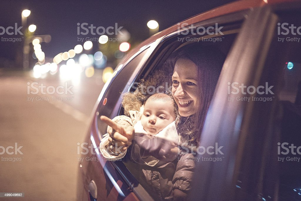 Mother pointing to the baby from the car stock photo
